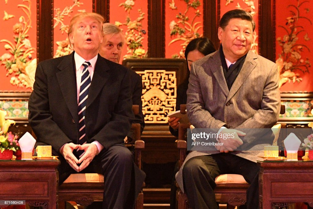 US President Donald Trump (L) looks up as he sits beside China's President Xi Jinping during a tour of the Forbidden City in Beijing on November 8, 2017. US President Donald Trump toured the Forbidden City with Chinese leader Xi Jinping on November 8 as he began the crucial leg of an Asian tour intended to build a global front against North Korea's nuclear threats. / AFP PHOTO / Jim WATSON