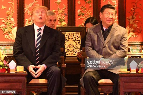 US President Donald Trump looks up as he sits beside China's President Xi Jinping during a tour of the Forbidden City in Beijing on November 8 2017...