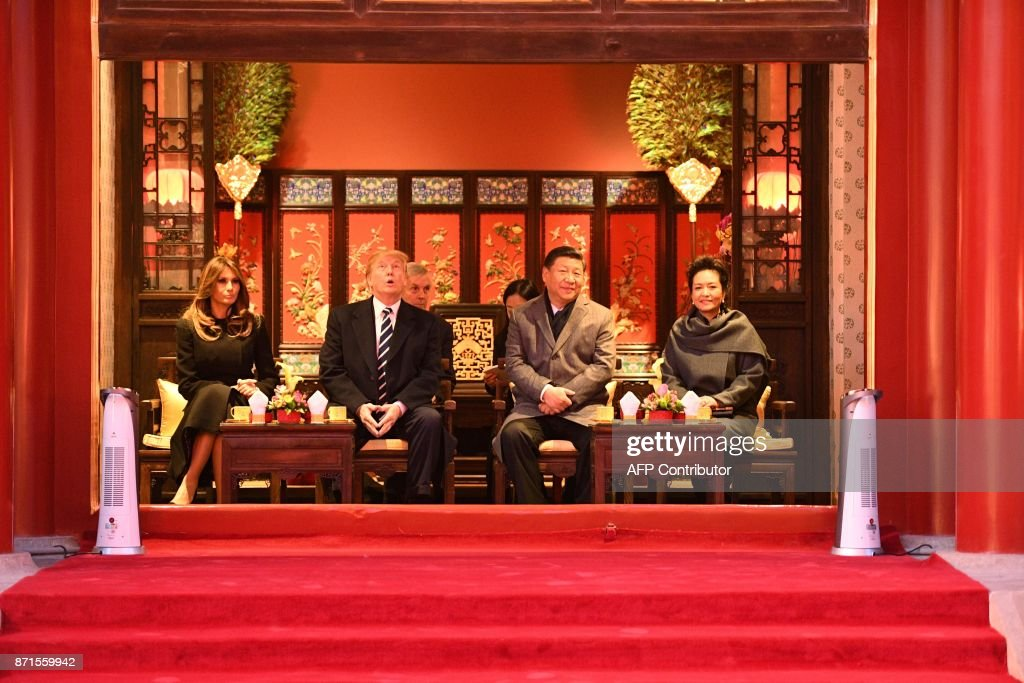 President Donald Trump (2nd L) looks up as he sits beside First Lady Melania Trump (L) and China's President Xi Jinping (2nd R) and his wife Peng Liyuan (R) during a tour of the Forbidden City in Beijing on November 8, 2017. US President Donald Trump toured the Forbidden City with Chinese leader Xi Jinping on November 8 as he began the crucial leg of an Asian tour intended to build a global front against North Korea's nuclear threats. / AFP PHOTO / Jim WATSON