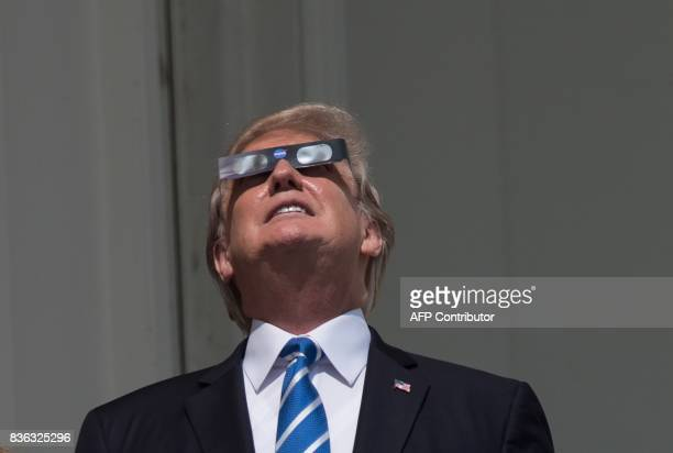 US President Donald Trump looks up at the partial solar eclipse from the balcony of the White House in Washington DC on August 21 2017 / AFP PHOTO /...