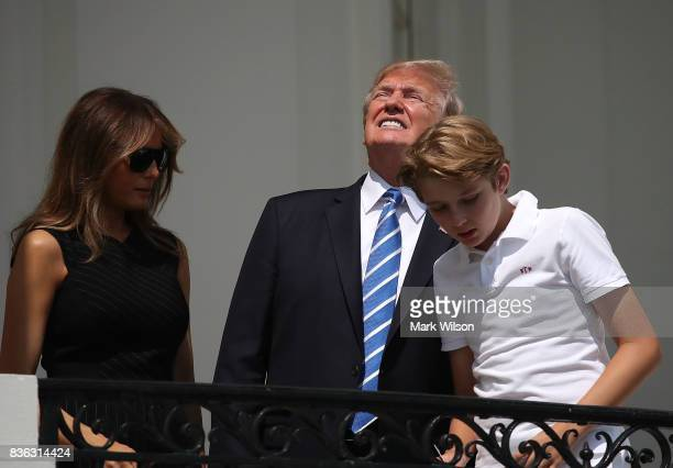 President Donald Trump looks up toward the Solar Eclipse while standing with his wife first lady Melania Trump and their son Barron, on the Truman...