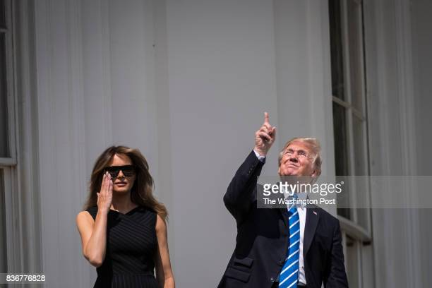 President Donald Trump looks up toward the Solar Eclipse with out glasses with first lady Melania Trump by his side from a balcony at the White House...