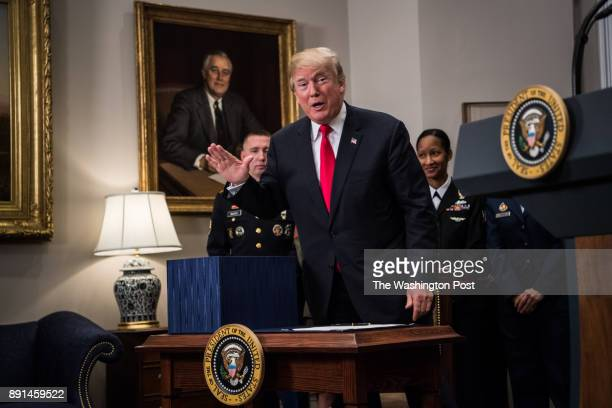 President Donald Trump makes a comment about the amount of pages a box containing the National Defense Authorization Act for Fiscal Year 2018 bill...