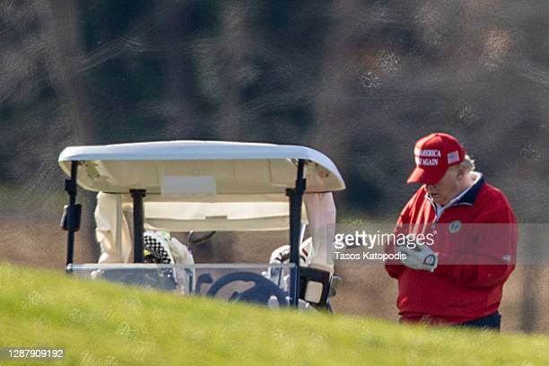 President Donald Trump makes a phone call as he golfs at Trump National Golf Club on November 26, 2020 in Sterling, Virginia. President Trump stayed...