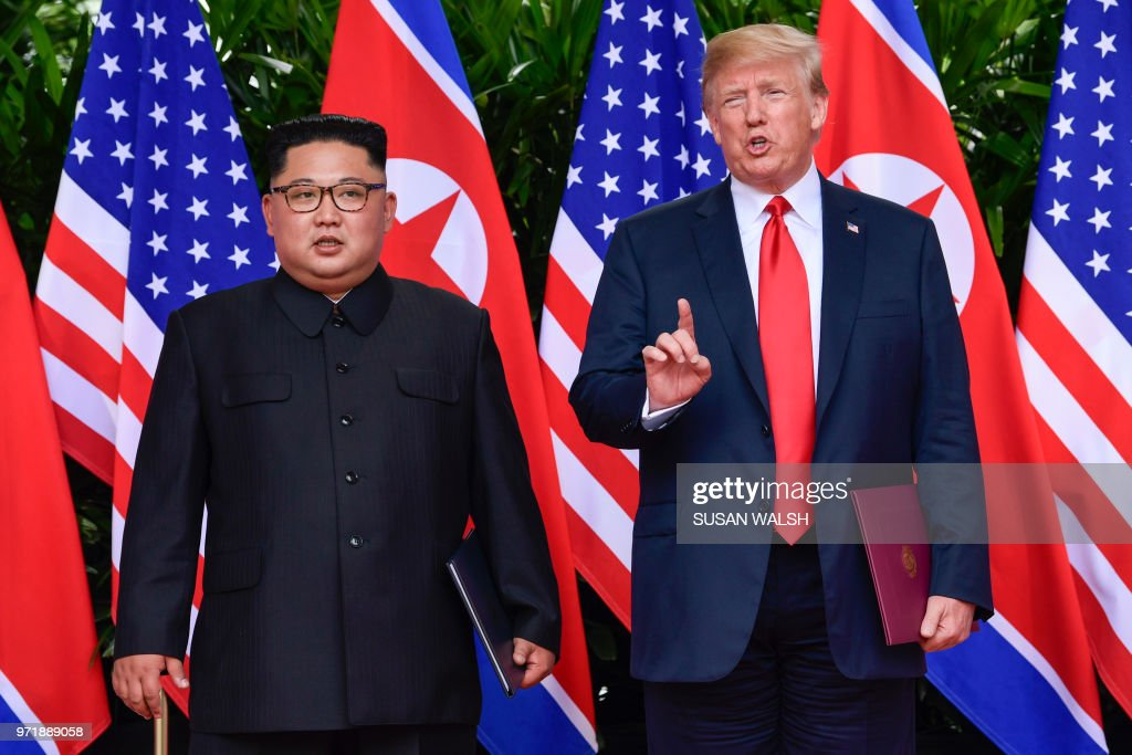 President Donald Trump makes a statement before saying goodbye to North Korea leader Kim Jong Un (L) after their meetings at the Capella resort on Sentosa Island in Singapore on June 12, 2018. - Donald Trump and Kim Jong Un became on June 12, the first sitting US and North Korean leaders to meet, shake hands and negotiate to end a decades-old nuclear stand-off.