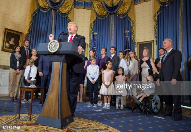 US President Donald Trump makes a statement on health care while standing with 'victims of Obamacare' at The White House on July 24 2017 in...