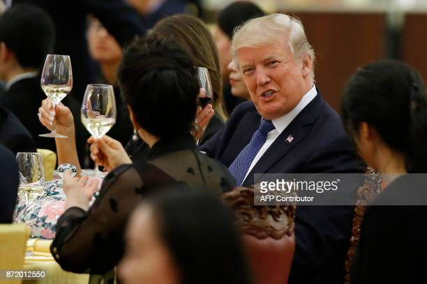 US President Donald Trump makes a toast to Peng Liyuan wife of China's President Xi Jinping during a state dinner in the Great Hall of the People in...