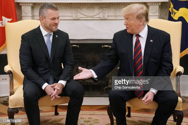 S President Donald Trump offers his hand to Slovak Republic Prime Minister Peter Pellegrini during a meeting in the Oval Office at the White House...