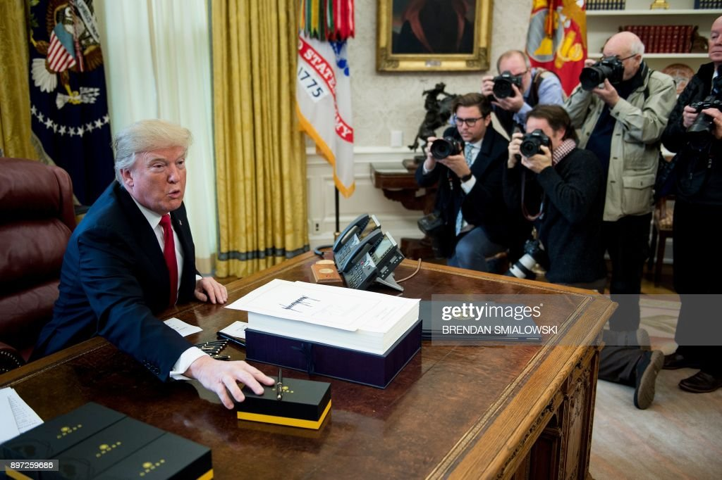 US President Donald Trump offers pens to the press after signing a tax reform bill in the Oval Office of the White House December 22, 2017 in Washington, DC. / AFP PHOTO / Brendan Smialowski