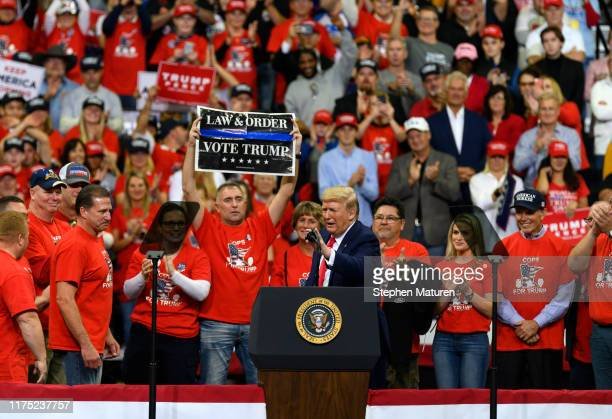 S President Donald Trump on stage with members of the Minneapolis Police Department during a campaign rally at the Target Center on October 10 2019...