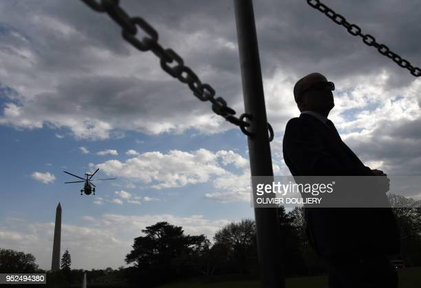 President Donald Trump onboard Marine One departs from the White House as a Secret Service agent stands guard on April 28 2018 in Washington DC...