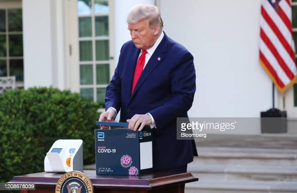 US President Donald Trump opens a Abbott Laboratories ID Now Covid19 test kit during a Coronavirus Task Force news conference in the Rose Garden of...