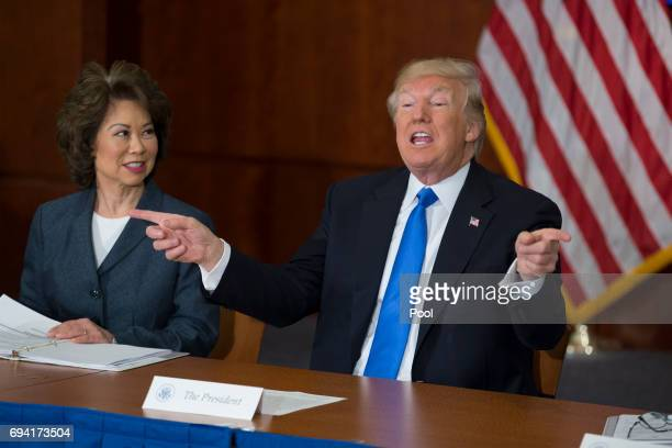 President Donald Trump participates in the 'Roads Rails and Regulatory Relief roundtable meeting' beside Secretary of Transportation Elaine Chao at...