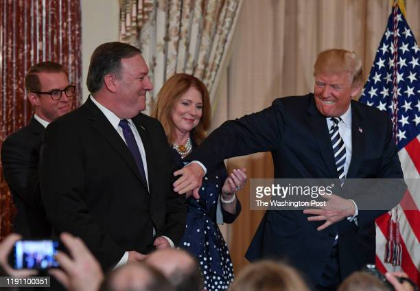 President Donald Trump pats Mike Pompeo on the arm after Pompeo was sworn in as the new Secretary of State while his family Nick left rear and wife...