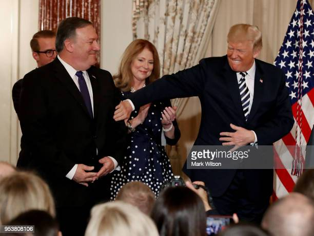 President Donald Trump pats Secretary of State Mike Pompeo during a ceremonial swearing in at the State Department on May 2 2018 in Washington DC...