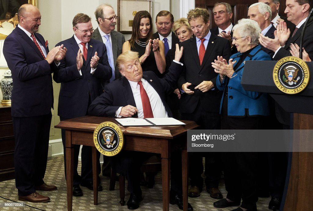 U.S. President Donald Trump pats the shoulder of Senator Rand Paul, a Republican from Kentucky, signing an executive order on health care in the Roosevelt Room of the White House in Washington, D.C., U.S., on Thursday, Oct. 12, 2017. Trumpsigned an executive order Thursday designed to expand health insurance options for some Americans, in a move that may also undermine coverage for those who remain in Obamacare. Photographer: T.J. Kirkpatrick/Bloomberg via Getty Images