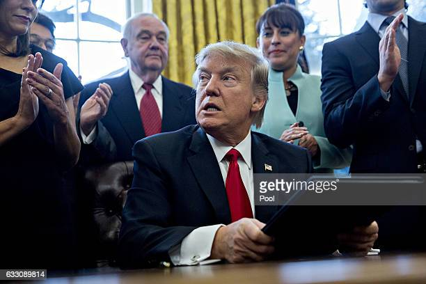 US President Donald Trump pauses after signing an executive order in the Oval Office of the White House surrounded by small business leadersJanuary...