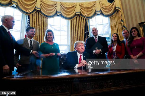 President Donald Trump pauses as he signs Executive Orders in the Oval Office of the White House, including an order to review the Dodd-Frank Wall...
