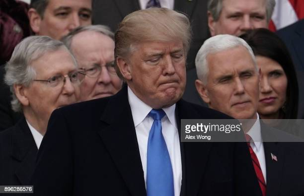 President Donald Trump pauses during an event to celebrate Congress passing the Tax Cuts and Jobs Act with Senate Majority Leader Sen. Mitch...