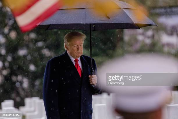 US President Donald Trump pauses while holding an umbrella to shelter from the rain during the American Commemoration Ceremony at the Suresnes...