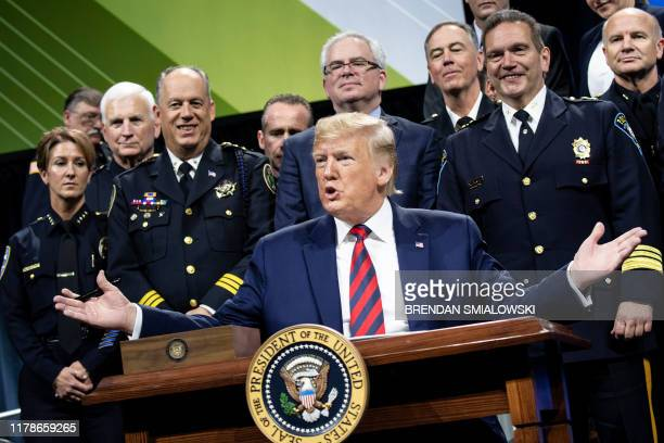 US President Donald Trump pauses while signing an executive order during the International Association of Chiefs of Police Annual Conference and...