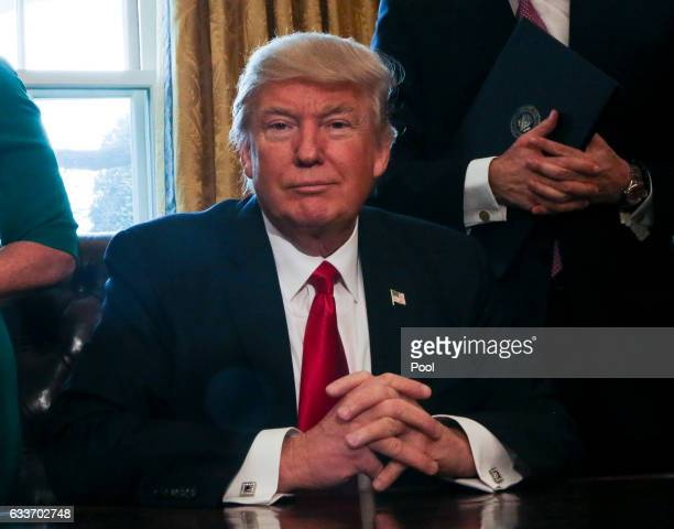 US President Donald Trump pauses while signning Executive Orders in the Oval Office of the White House including an order to review the DoddFrank...
