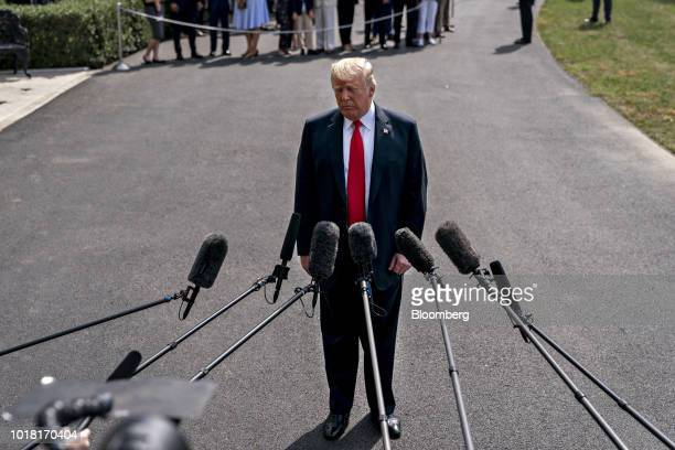 US President Donald Trump pauses while speaking to members of the media before boarding Marine One on the South Lawn of the White House in Washington...