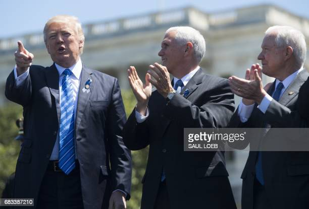 President Donald Trump points alongside US Vice President Mike Pence and Attorney General Jeff Sessions during the 36th Annual National Peace...