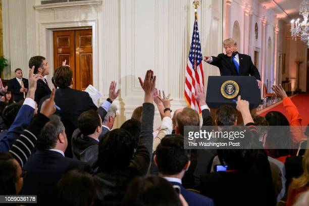 President Donald Trump points at reporters who raise their hands to ask questions during a press conference in the East Room of the White House in...