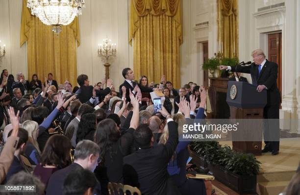US President Donald Trump points to journalist Jim Acosta from CNN during a postelection press conference in the East Room of the White House in...