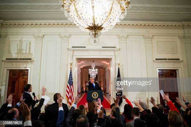 US President Donald Trump points to reporters during a news conference a day after the midterm elections on November 7 2018 in the East Room of the...