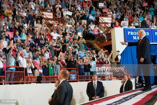 US President Donald Trump points to supporters as he arrives to speak during a 'Make America Great Again' rally in Harrisburg PA April 29 marking...