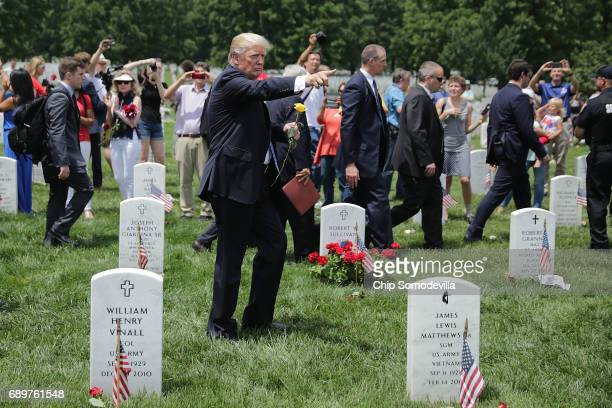 S President Donald Trump points while walking through Section 60 at Arlington National Cemetery on Memorial Day May 29 2017 in Arlington Virginia...