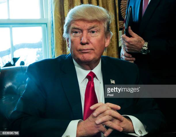S President Donald Trump poses after signing Executive Orders in the Oval Office of the White House including an order to review the DoddFrank Wall...