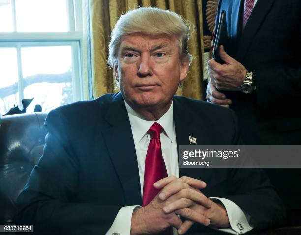 US President Donald Trump poses for photographs after signing an Executive Order related to the review of the DoddFrank Act in the Oval Office of the...