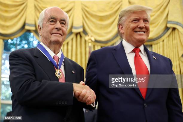 S President Donald Trump poses for photographs with automotive businessman and racing legend Roger Penske after he was presented with the...
