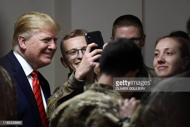 US President Donald Trump poses for selfies during a Thanksgiving dinner with US troops at Bagram Air Field during a surprise visit on November 28...