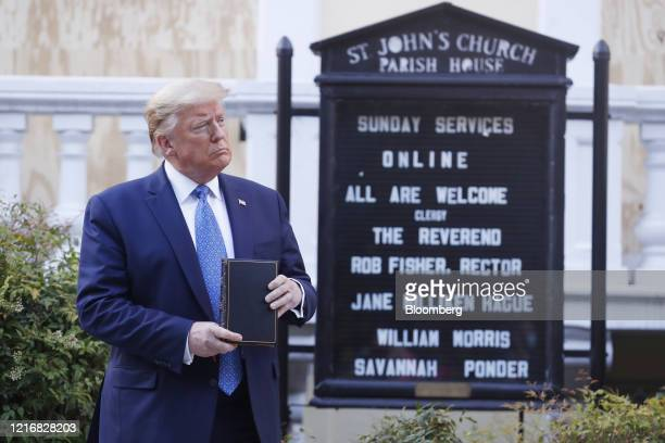 US President Donald Trump poses with a bible outside St John's Episcopal Church after a news conference in the Rose Garden of the White House in...