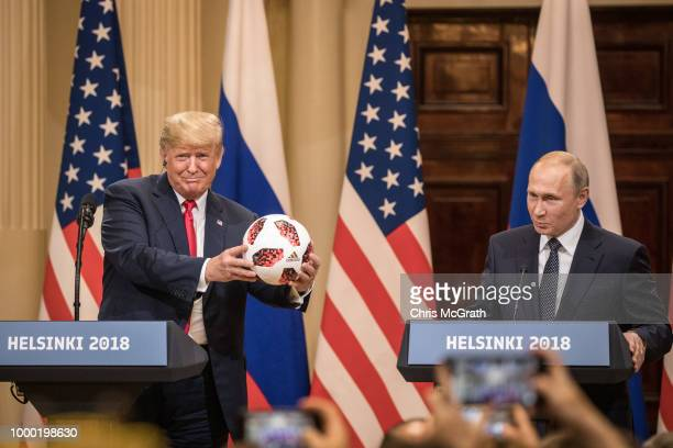 S President Donald Trump poses with a football given to him by Russian President Vladimir Putin during a joint press conference after their summit on...