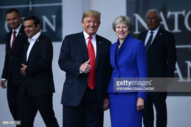 US President Donald Trump poses with Britain's Prime Minister Theresa May as NATO leaders gather for a family photo ahead of the opening ceremony for...