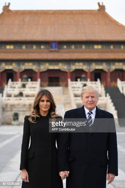 US President Donald Trump poses with First Lady Melania Trump in the Forbidden City in Beijing on November 8 2017 US President Donald Trump arrived...