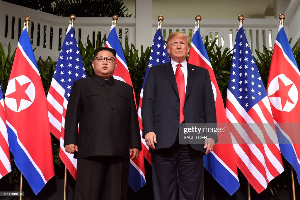 President Donald Trump (R) poses with North Korea's leader Kim Jong Un (L) at the start of their historic US-North Korea summit, at the Capella Hotel on Sentosa island in Singapore on June 12, 2018. - Donald Trump and Kim Jong Un have become on June 12 the first sitting US and North Korean leaders to meet, shake hands and negotiate to end a decades-old nuclear stand-off.