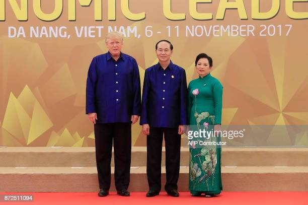 US President Donald Trump poses with Vietnams President Tran Dai Quang as his wife Nguyn Th Hin upon arrival for the AsiaPacific Economic Cooperation...