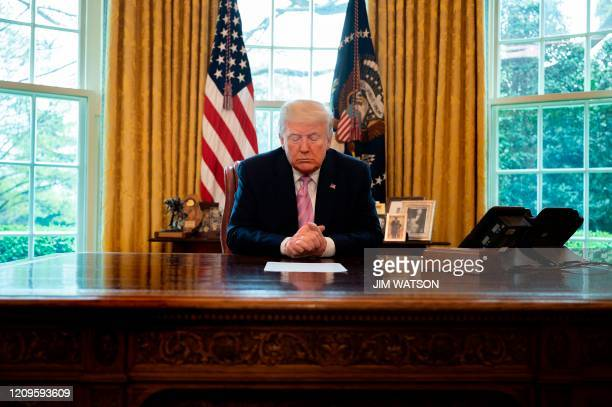 President Donald Trump prays at his desk as he participates in an Easter Blessing with Bishop Harry Jackson at the White House in Washington, DC, on...