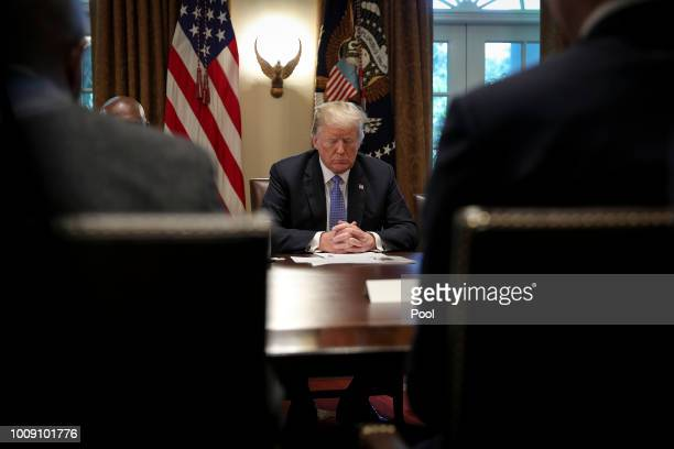 US President Donald Trump prays during a meeting with inner city pastors in the Cabinet Room of the White House on August 1 2018 in Washington DC