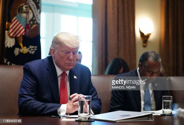 US President Donald Trump prays next to Ben Carson Secretary of Housing and Urban Development as they take part in a cabinet meeting in the Cabinet...