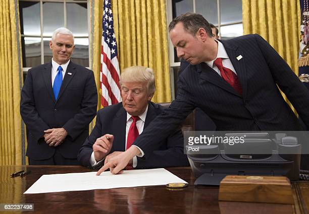 President Donald Trump prepares to sign a confirmation for Defense Secretary James Mattis as his Chief of Staff Reince Priebus points to the order...