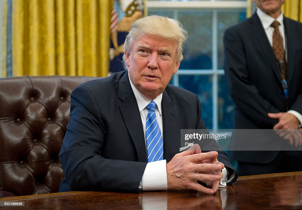 U.S. President Donald Trump prepares to sign three Executive Orders in the Oval Office of the White House in Washington, DC on Monday, January 23, 2017. These concerned the withdrawal of the United States from the Trans-Pacific Partnership (TPP), a US Government hiring freeze for all departments but the military, and 'Mexico City' which bans federal funding of abortions overseas.
