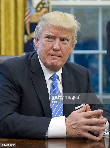 US President Donald Trump prepares to sign three Executive Orders in the Oval Office of the White House in Washington DC on Monday January 23 2017...