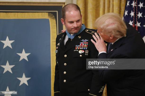 President Donald Trump presents Army Master Sgt. Matthew Williams of Boerne, Texas, with the Medal of Honor during a ceremony in the East Room of the...